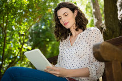 Femme s'asseyant sur le banc et à l'aide du comprimé numérique dans le jardin un jour ensoleillé Image libre de droits