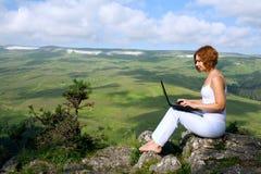 Femme s'asseyant sur le bord d'une falaise avec un ordinateur portatif Photo stock