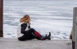 Femme s'asseyant sur le bord du pilier en hiver regardant la La congelée photos libres de droits