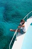 Femme s'asseyant sur le bord du yacht Photos stock