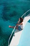 Femme s'asseyant sur le bord du yacht Photo stock