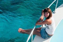 Femme s'asseyant sur le bord du yacht Image stock
