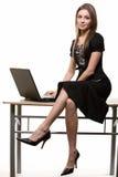 Femme s'asseyant sur le bureau Photographie stock libre de droits