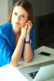 Femme s'asseyant sur le bureau avec l'ordinateur portable Photos stock