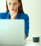 Femme s'asseyant sur le bureau avec l'ordinateur portable Image stock