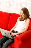 Femme s'asseyant sur le divan avec l'ordinateur portatif Photographie stock libre de droits