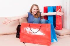 Femme s'asseyant sur le divan avec le panier autour de l'action joyeuse Images libres de droits