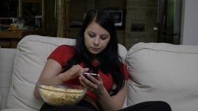 Femme s'asseyant sur le divan avec un bol de maïs éclaté et textotant au téléphone intelligent pendant la coupure de publicité té banque de vidéos