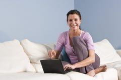 Femme s'asseyant sur le divan à la maison avec l'ordinateur portatif Photos stock