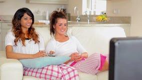 Femme s'asseyant sur le divan regardant la TV banque de vidéos