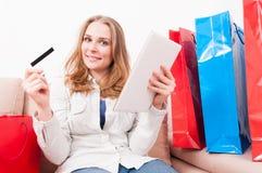 Femme s'asseyant sur le divan tenant le comprimé montrant la carte de crédit Image libre de droits