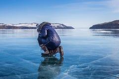 Femme s'asseyant sur le lac Baïkal congelé Images libres de droits