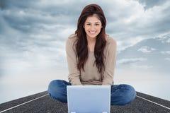 Femme s'asseyant sur le lit avec l'ordinateur portable devant elle et le sourire Photos libres de droits