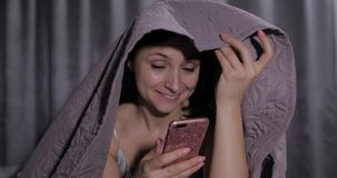 Femme s'asseyant sur le lit sous la couverture et appr?ciant la causerie ? l'ami sur le smartphone banque de vidéos
