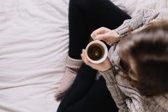 Femme s'asseyant sur le lit, thé potable photos libres de droits