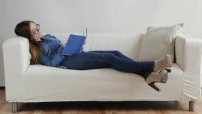 Femme s'asseyant sur le livre de lecture de divan à la maison Plein HD 1920x1080p banque de vidéos
