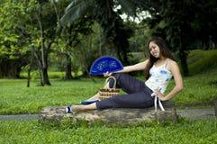 Femme s'asseyant sur le logarithme naturel avec le ventilateur ouvert Image libre de droits