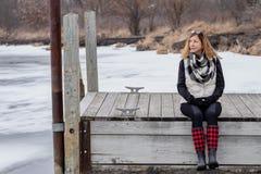 Femme s'asseyant sur le pilier en bois en hiver regardant au-dessus de l gelé images stock
