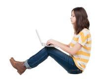 Femme s'asseyant sur le plancher avec l'ordinateur portable Photographie stock