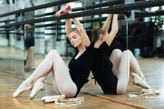 Femme s'asseyant sur le plancher dans la classe de ballet photo libre de droits