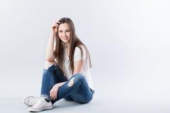 Femme s'asseyant sur le plancher et le sourire Photos stock