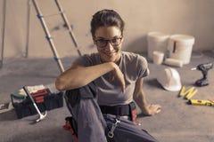 Femme s'asseyant sur le plancher et prévoyant une rénovation à la maison photo libre de droits