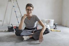 Femme s'asseyant sur le plancher et prévoyant une rénovation à la maison photos stock