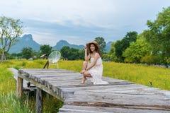 Femme s'asseyant sur le pont en bois avec le gisement de fleur jaune de cosmos image stock