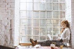 Femme s'asseyant sur le rebord de fenêtre avec le carnet Images stock