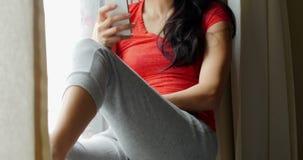 Femme s'asseyant sur le rebord de fenêtre et à l'aide du téléphone portable clips vidéos