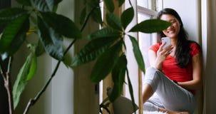 Femme s'asseyant sur le rebord de fenêtre et à l'aide du téléphone portable banque de vidéos