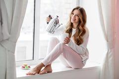 Femme s'asseyant sur le rebord de fenêtre et le thé ou le café se renversant de la bouilloire Images stock