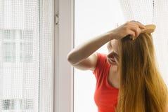 Femme s'asseyant sur le rebord de fenêtre se brossant les cheveux Photographie stock