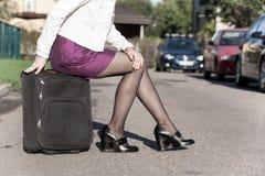 Femme s'asseyant sur le sac de voyage sur la rue, étant prête pour le jorney Photographie stock