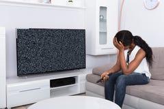 Femme s'asseyant sur le signal de Sofa Near Television With No photos libres de droits
