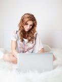 Femme s'asseyant sur le sofa avec l'ordinateur portable image libre de droits