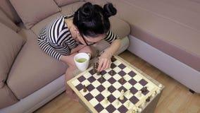Femme s'asseyant sur le sofa et jouant des échecs Vue supérieure banque de vidéos