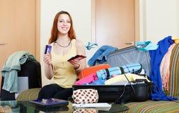 Femme s'asseyant sur le sofa et la valise de emballage photo libre de droits