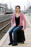 Femme s'asseyant sur le train de attente de bagage Images libres de droits