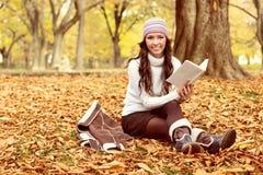 Femme s'asseyant sur les feuilles d'automne et le livre de lecture Images stock
