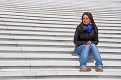Femme s'asseyant sur les opérations de marbre Photographie stock