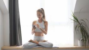 Femme s'asseyant sur les vidéos de observation de filon-couche de fenêtre sur le smartphone et les écouteurs banque de vidéos