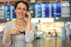 Femme s'asseyant sur leur bagage dans le hall de l'aéroport Photos libres de droits