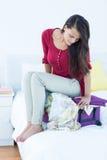 Femme s'asseyant sur sa valise Photo stock
