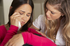 Femme s'asseyant sur Sofa Comforting Unhappy Friend Photo stock
