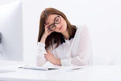 Femme s'asseyant sur son lieu de travail avec les yeux fermés photos stock