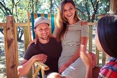 Femme s'asseyant sur son man& x27 ; genoux de s tout en écoutant son ami Image stock