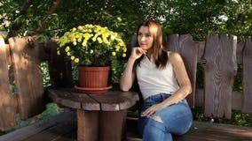 Femme s'asseyant sur un banc à la nuance des arbres Caché du roussissement, le soleil chaud Repos après une promenade banque de vidéos