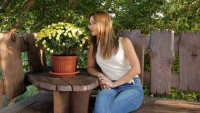 Femme s'asseyant sur un banc à la nuance des arbres femme sentant les fleurs jaunes dans des pots banque de vidéos