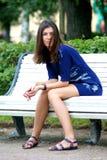 Femme s'asseyant sur un banc Image stock